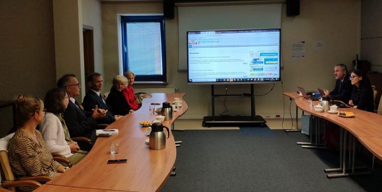 Zdjęcie przedstawia uczestników spotkania siedzących przy stołach w sali konferencyjnej