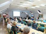 """Uczestnicy warsztatów szkoleniowych """"INFO-OŚRODEK"""" siedza przy podłużnych stołach i słuchają prezentacji"""