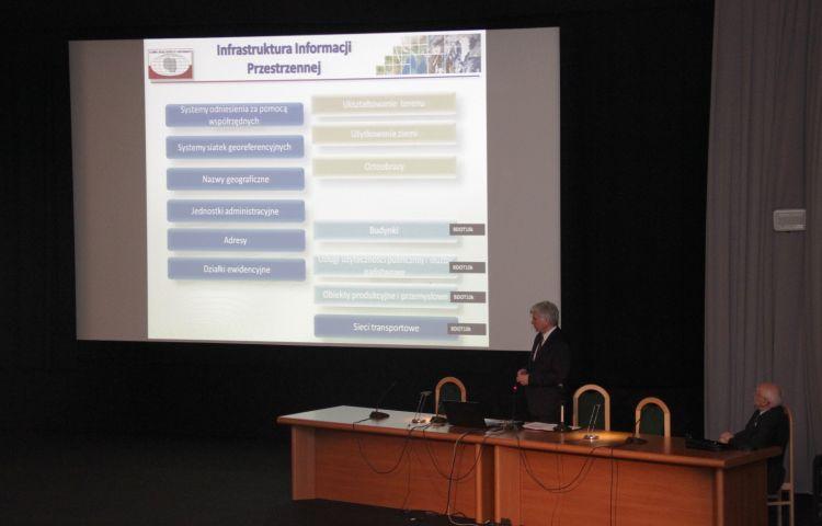 Główny Gedoeta Kraju za stołem omawia widoczen na ekranie tematy danych przestrzennych wymienine w ustawie o IIP