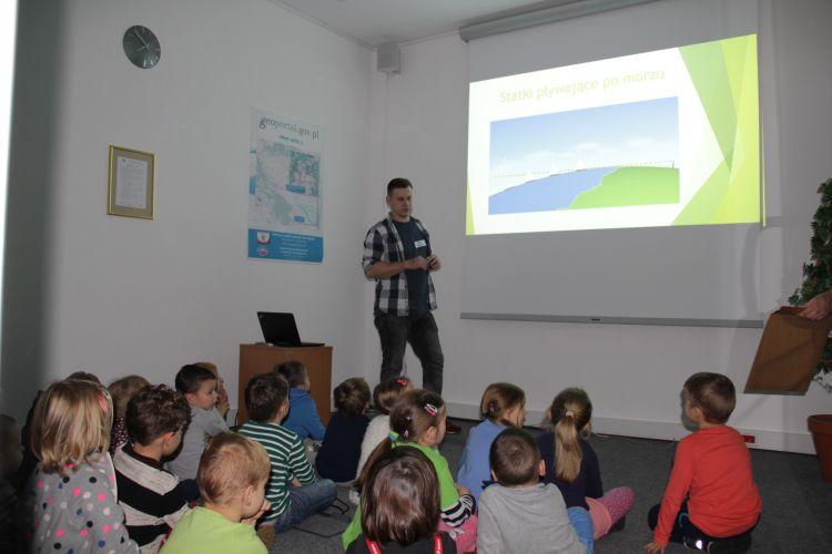 Prezentacja - geodezja dla najmłodszych. Czyli o horyzoncie i nie tylko.Dziecie siedzące przez ekranem. Na ekranie obraz morza i statku na horyzoncie