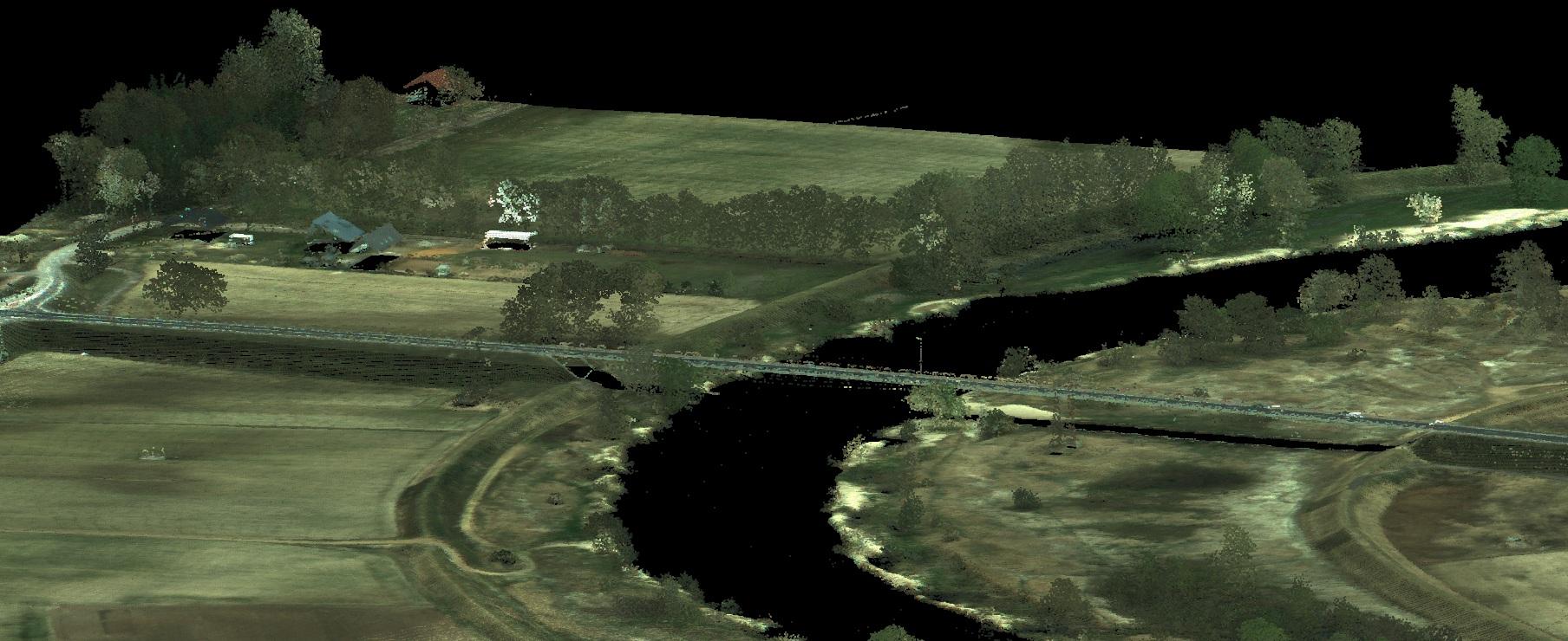 Wizualizacja atrybutów RGB danych ALS pozwala na odwzorowanie kolorów skanowanego terenu. Na obrazie tereny zielone łaki i drzewa, rzeka w kolorze czarnym, białe budynki po lewej stronie