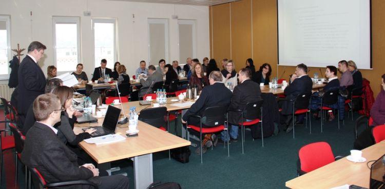 Ujęcie na salękonferencyjną z uczestnikami spotkania. Po lewej stronie stół prezydialny