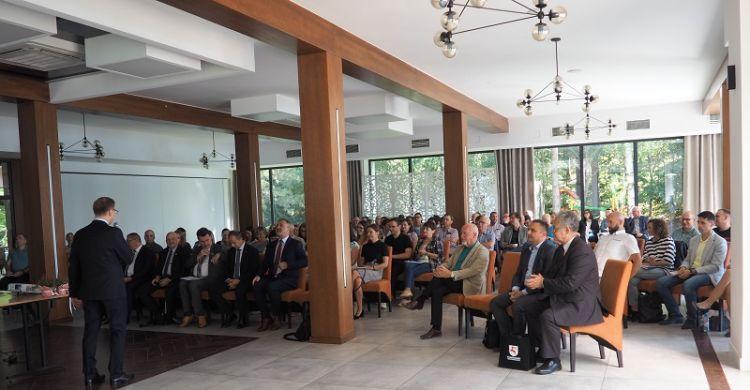 Zdjęcie przedstawia uczestników konferencji słuchających przemawiającego Kujawsko-Pomorskiego Wojewódzki Inspektor Nadzoru Geodezyjnego i Kartograficznego Roberta Cieszyńskiego