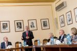 Główny Geodeta Kraju przemawia na uroczystości podpisania listu intencyjnego w Katowicach. GGK stoi za stołem ustawionym w podkowę obok uczestnicy spotkania
