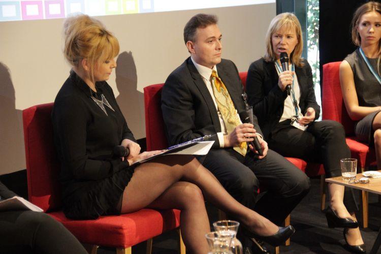 Trzy osoby siedzące na krzesłach. Pierwsza od prawej Agnieszka Gruchała opowiada o serwisie Geoportalu